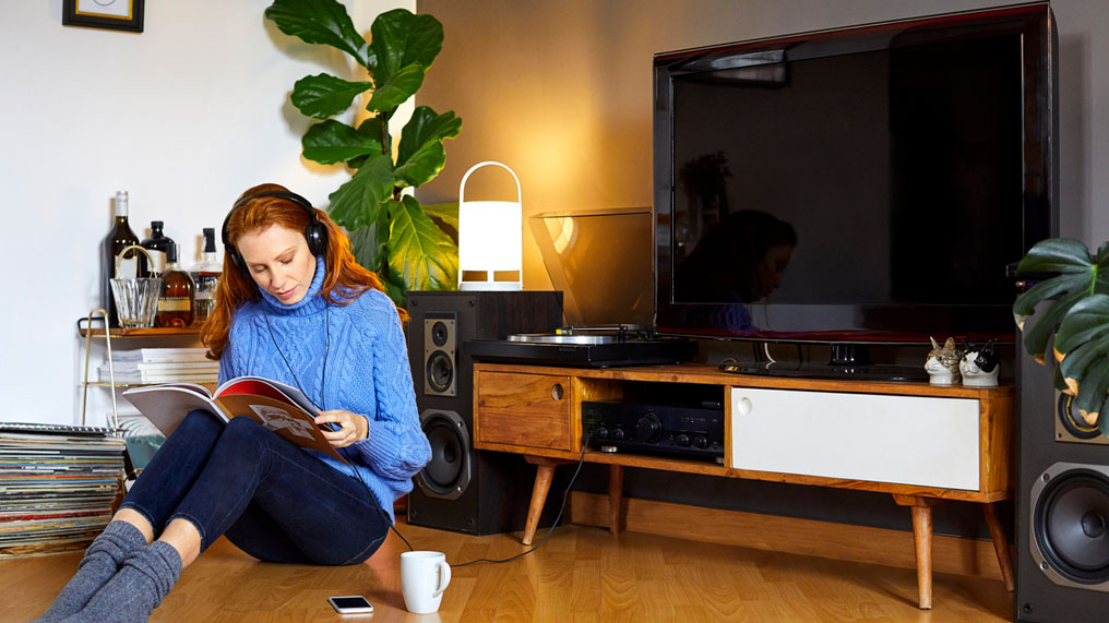 Woman sitting listening to her headphones at home