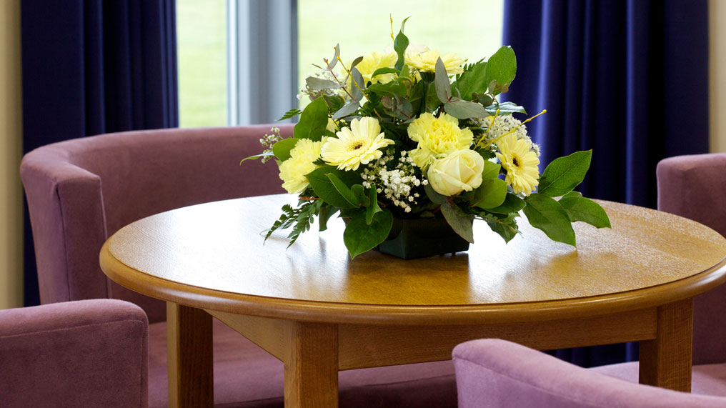A flower in the centre of a table at a funeral director's.
