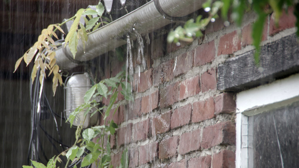 Gutters outside a house are being overwhelmed by rainwater.