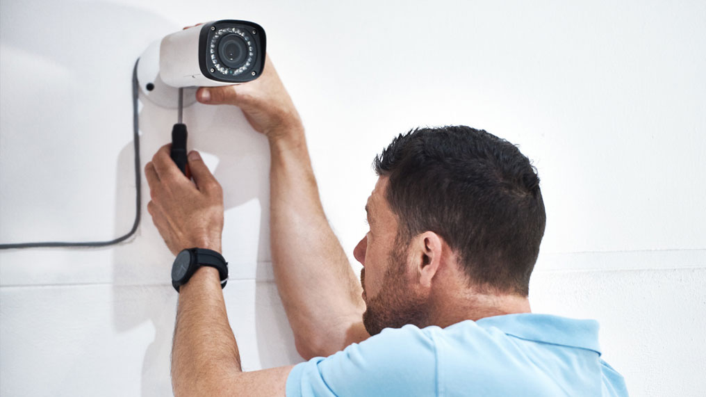 A man installs a security camera.