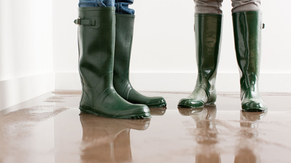 Two people wear wellington boots while stood in a flooded house.