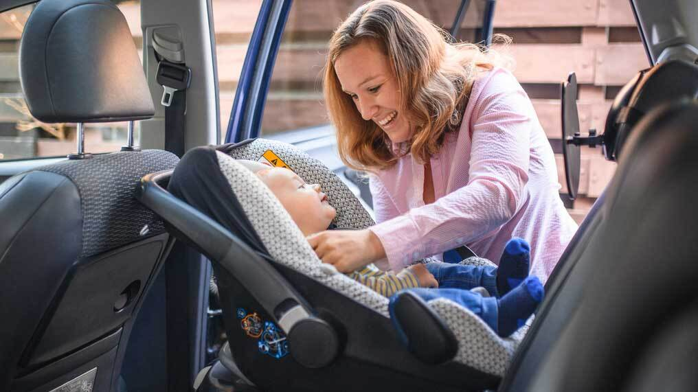 A baby is safely placed in a rear-facing car seat.